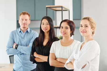 Portret młodego wieloetnicznego zespołu biznesowego stojącego razem ze skrzyżowanymi rękami i uśmiechającego się do kamery w biurze