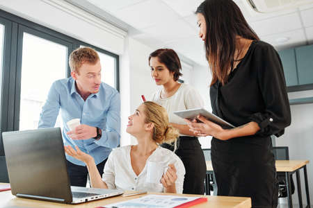 Business people talking to young businesswoman while she sitting at the table with laptop computer and explaining them the way of work they working at office