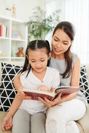 Young mother teaching her little daughter to read a book while they sitting on sofa and spending leisure time at home