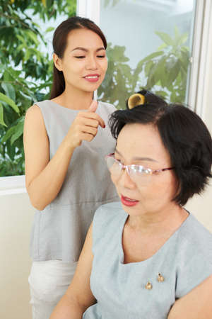Mature Asian woman sitting while hairdresser making a hairstyle in hair salon