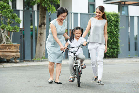 Asian mother and grandmother teaching their little girl to ride on bicycle in the park
