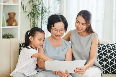 Happy Asian family of three sitting on sofa with sheets of papers and reading letters together in the living room at home