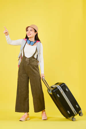 Happy curious young Asian woman with suitcase pointing with her finger