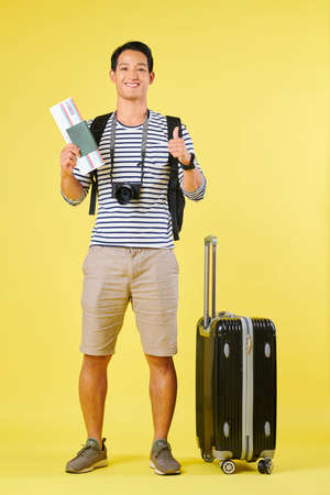Excited young man in striped t-shirt standing next to his suitcase and showing thumbs-up