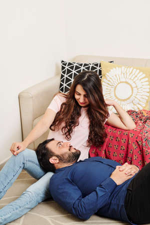 Bearded Indian man resting his head on laps of his girlfriend and looking in her eyes with love and tender Banco de Imagens