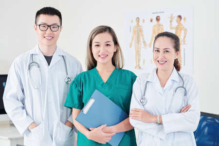 Team of smiling Vietnamese general practitioner, syrgeon and