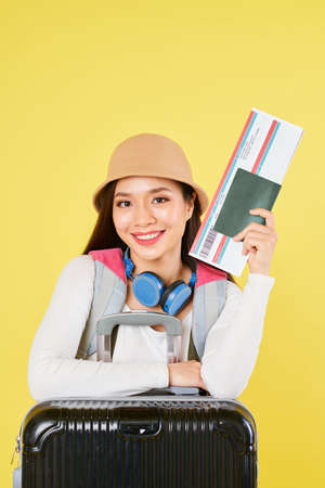 Cheerful young Asian woman in panama hat leaning on her suitcase with passport and boarding pass Фото со стока