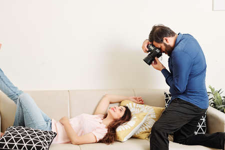 Smiling beautifulf young Indian woman lying on sofa and posing for professional photographer