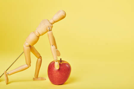 Wooden man playing with red fresh apple on yellow studio background Banque d'images - 128303454