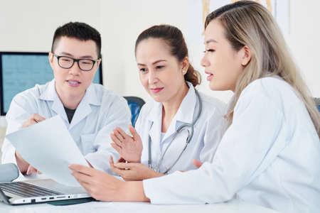 Equipo de médicos asiáticos experimentados que leen el documento y discuten el historial médico del paciente en la reunión