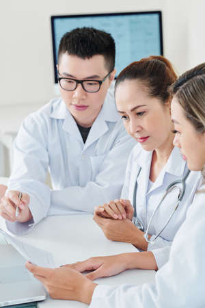 Group of professional doctors gathered together to discuss document explaining new method of treatment 写真素材