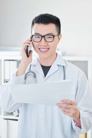 Portrait of smiling positive Vietnamese doctor in glasses holding medical history when talking on phone