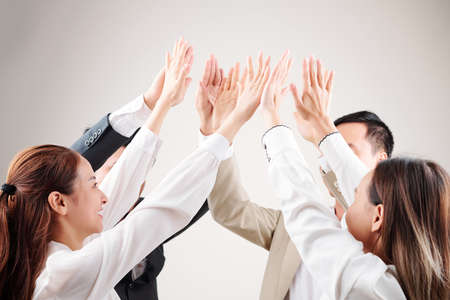 Group of Asian business people raising their arms up giving a high five to each other and celebrating their success