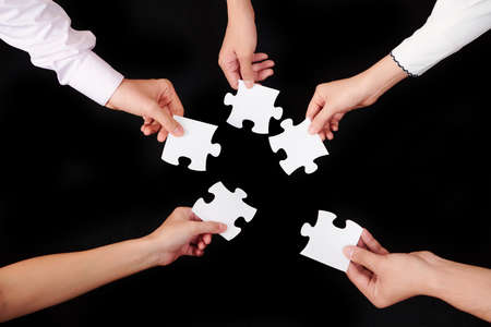 Close-up of business people holding pieces of puzzles and trying to connect them over black background Reklamní fotografie