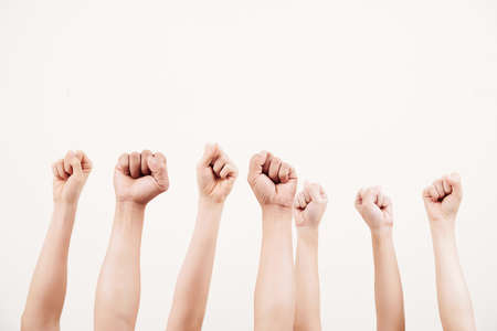Close-up of business group raising their fists up and demonstrating power isolated on white background Archivio Fotografico