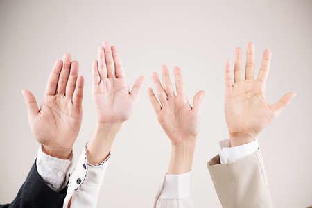 Close-up of multiethnic business people raising their arms up and waving over white background