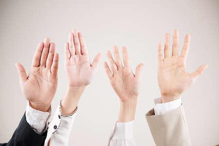 Nahaufnahme von multiethnischen Geschäftsleuten, die ihre Arme heben und auf weißem Hintergrund winken