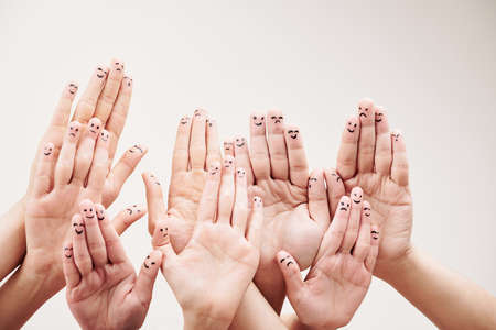 Close-up of group of people showing smileys on their fingers of hands against the white background