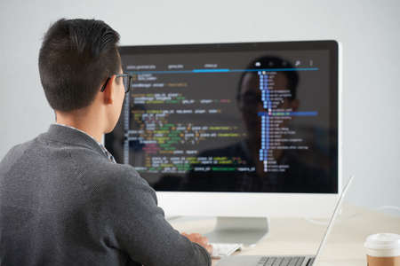 Rear view of young programmer sitting at the table in front of computer monitor and developing new application at office