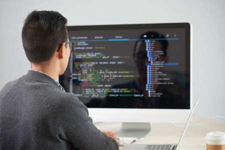 Vista trasera del joven programador sentado en la mesa frente al monitor de la computadora y desarrollando una nueva aplicación en la oficina Foto de archivo