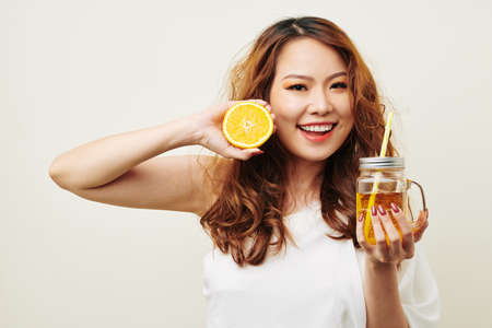 Portrait of Asian smiling young woman with red long curly hair holding orange fruit in one hand and glass with orange juice in other hand isolated Stock Photo
