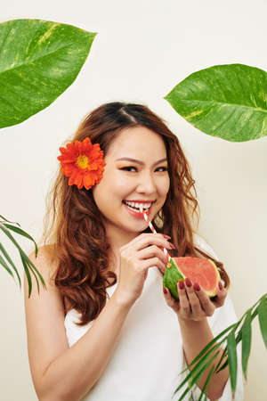 Portrait of Asian model drinking watermelon juice from drinking straw and smiling at camera with green leaves around her on white background