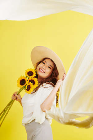 Portrait of Asian young woman in hat holding bouquet of sunflowers and smiling at camera isolated on yellow background