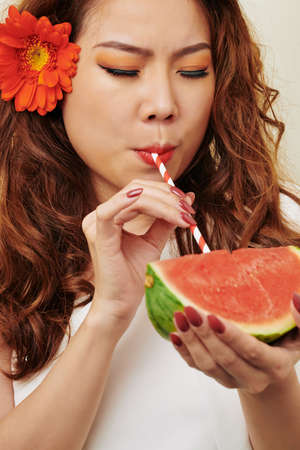 Beautiful Asian woman with flower in her long hair drinking watermelon juice from drinking straw