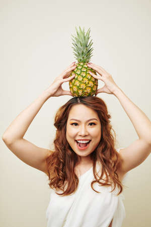 Portrait of excited Asian girl with red long curly hair holding pineapple over her head and smiling at camera isolated on white background 版權商用圖片