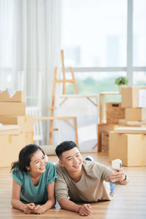 Young Asian couple lying on the floor and smiling they making selfie portrait on mobile phone in their new home
