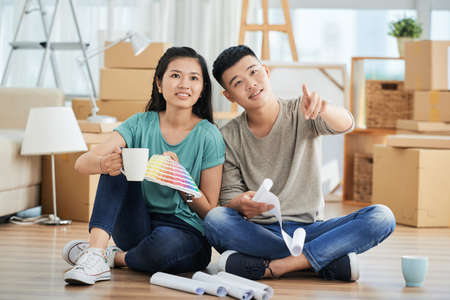 Asian young couple sitting on the floor drinking coffee and discussing their repair in new apartment