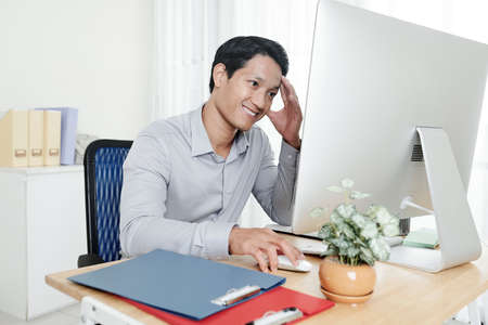 Smiling young Asian businessman touching forehead when reading report on screen of computer
