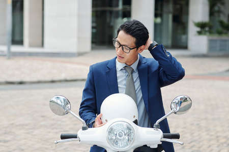 Young businessman taking off helmet and touching his hair after riding to office Stock Photo