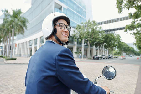 Smiling young Asian businessman looking around when riding scooter in the city