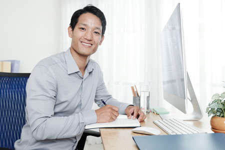 Young smiling Vietnamese entrepreneur writing plans and ideas in his journal when sitting at office table