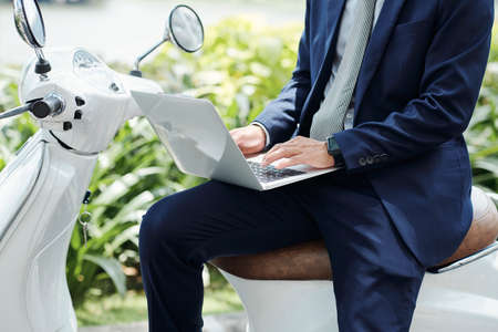 Cropped image of male digital nomad sittig on scooter and answering e-mails or communicating with clients