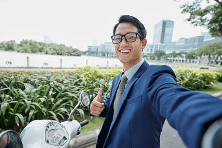 Happy excited young Vietnamese businessman smiling and showing thumbs-up when taking selfie outdoors