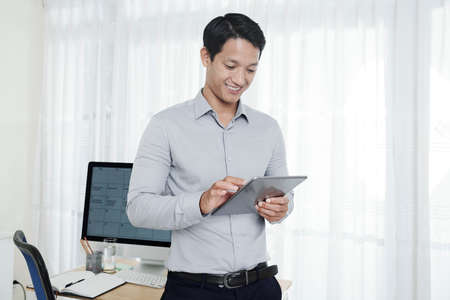 Cheerful young handsome entrepreneur using application on tablet computer when working in office Reklamní fotografie