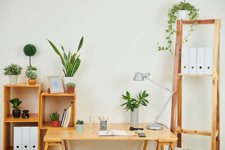 Image of modern workplace with wooden table and notepad on it and different kinds of green plants on the shelves