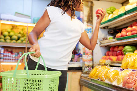 African young woman standing with shopping basket and choosing a fresh ripe apples in the supermarket