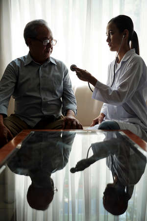 Young doctor sitting in front of the table with senior man talking to him and she is going to listen to his heartbeat with stethoscope