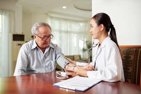 Aziatische jonge verpleegster die samen met een oudere man aan tafel zit en zijn bloeddruk onderzoekt tijdens haar bezoek thuis