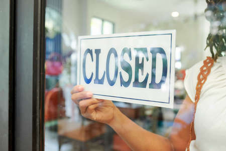 Close-up of saleswoman hanging the Closed sign on glass door and closed the store Imagens