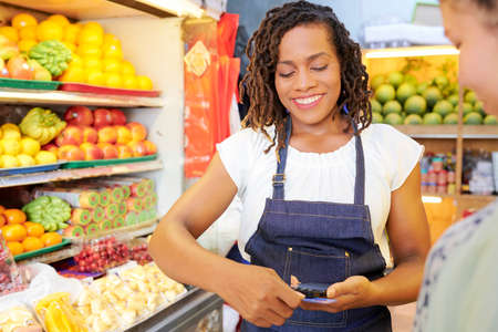 Close-up of African saleswoman in apron holding mobile phone and making a purchase with credit card in the supermarket