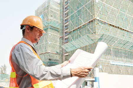 Young engineer in hardhat and reflective clothing examining blueprint while standing outdoors opposite the building under construction