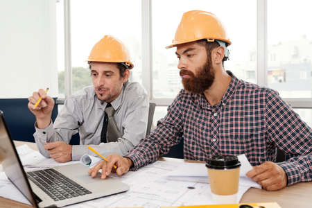 Two architects wearing hardhats sitting at the table using laptop computer and discussing working moments together at office