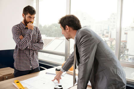 Businessman in suit standing near the table pointing at blueprint and discussing some working moments with architect who listening to hime at office