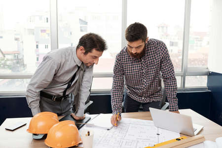Two young businessmen standing near the table looking at blueprint on it and discussing some moments together at office Banco de Imagens