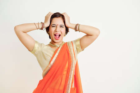 Young woman in traditional sari dress touching her head and shouting