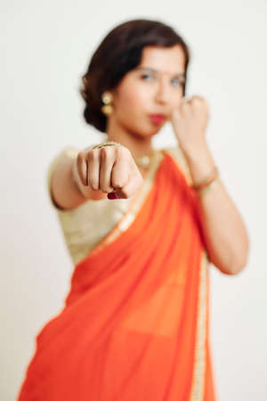 Young Indian woman in sari clenching fists with anger and getting ready to fight for her rights